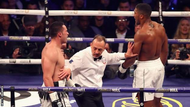 Boxing referee holds Anthony Joshua and Joseph Parker apart