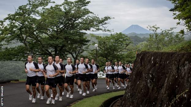 Mt. Fuji is seen in the background as keirin students run up a hill