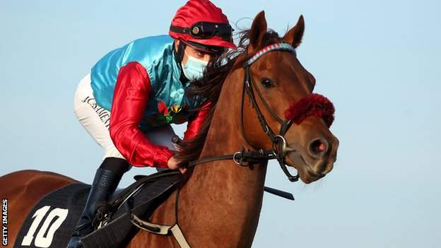 A jockey wearing a face mask while riding