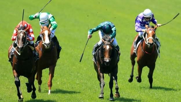 Jockeys using whips during a race