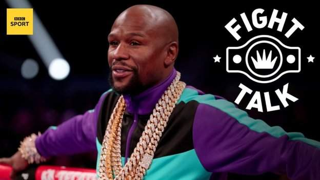 Former world champion Floyd Mayweather leans against the rope while wearing a gold chain an tracksuit top