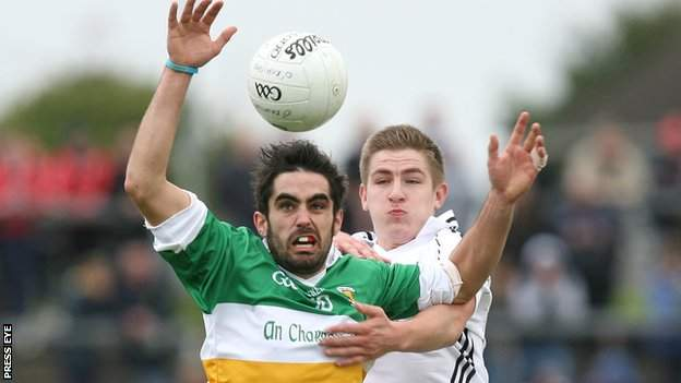 Carrickmore's Michael McCallan battles with Clonoe's Dwayne Quinn
