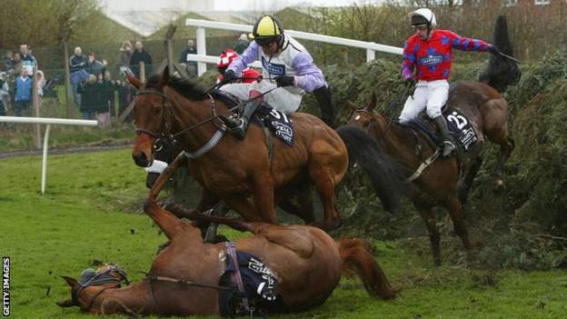 Warren Marston on Ardent Scout takes evasive action to avoid the fallen horse Bounce Back ridden by Andrew Thornton after they jumped Becher's Brook in the 2004 National