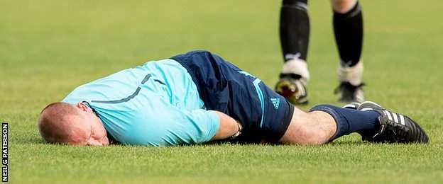 Referee Robert Baxter lies injured on the turf