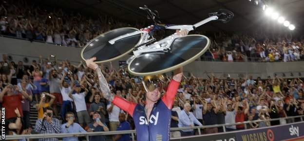 Sir Bradley Wiggins holds his bike aloft after breaking the record