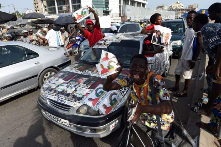 Supporters present posters of current Prime Minister Lionel Zinsou, a French-Beninese investment banker and candidate of the ruling party Cowrie Forces for an Emerging Benin (FCBE) during a rally in Cotonou, on March 3, 2016.