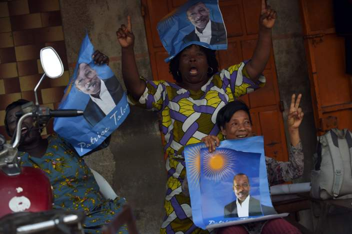 Supporters hold up posters of cotton tycoon and presidential candidate Patrice Talon during a rally in Cotonou, on March 3, 2016. Benin goes to the polls on March 6, 2016 to elect a new president, with a record number of candidates standing, including two of the country's most influential businessmen.