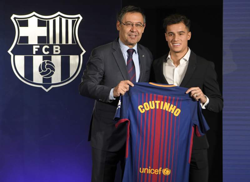 Philippe Coutinho poses with a Barcelona shirt alongside club president Josep Bartomeu.
