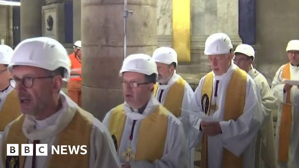 Priests wear hard hats at Notre-Dame thumbnail