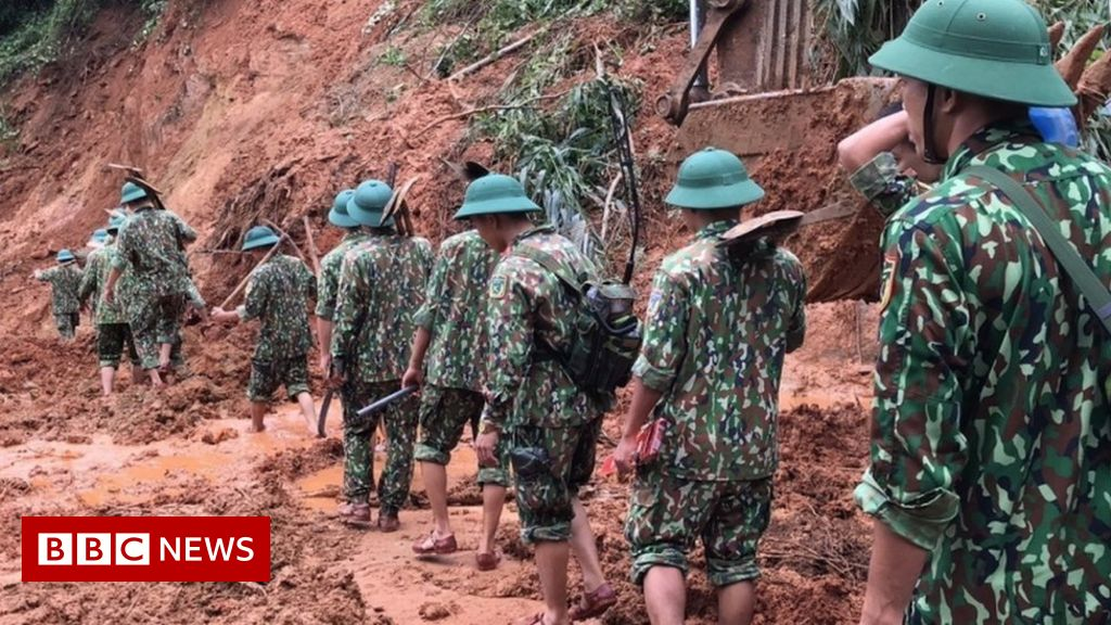 Vietnam landslide: Rescuers search for survivors at barracks
