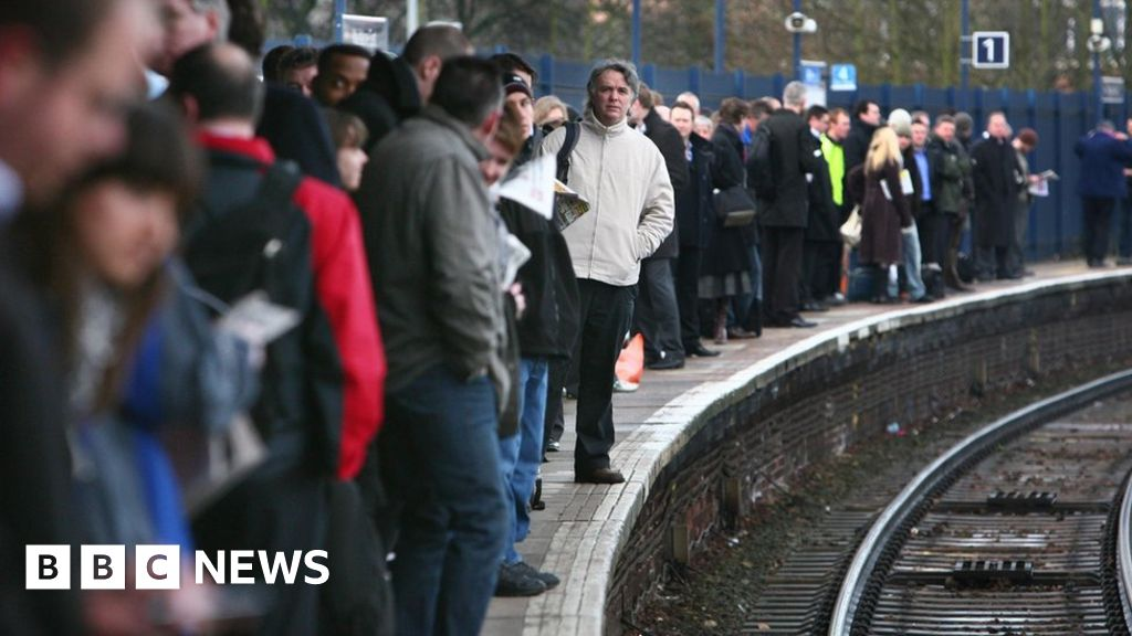 People waiting for trains on a platform
