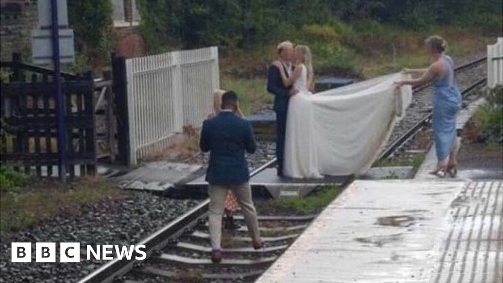 Couple posed on rail line for wedding shoot