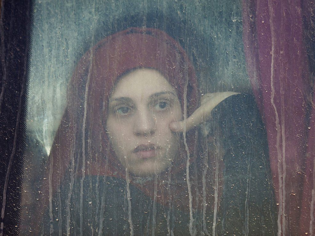 A young woman looks out of a window of a bus