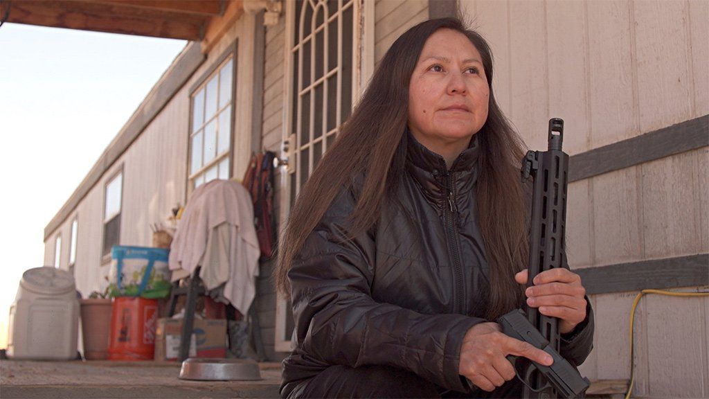 Shiprock resident Bea Redfeather sits on her porch holding guns she bought to protect her family