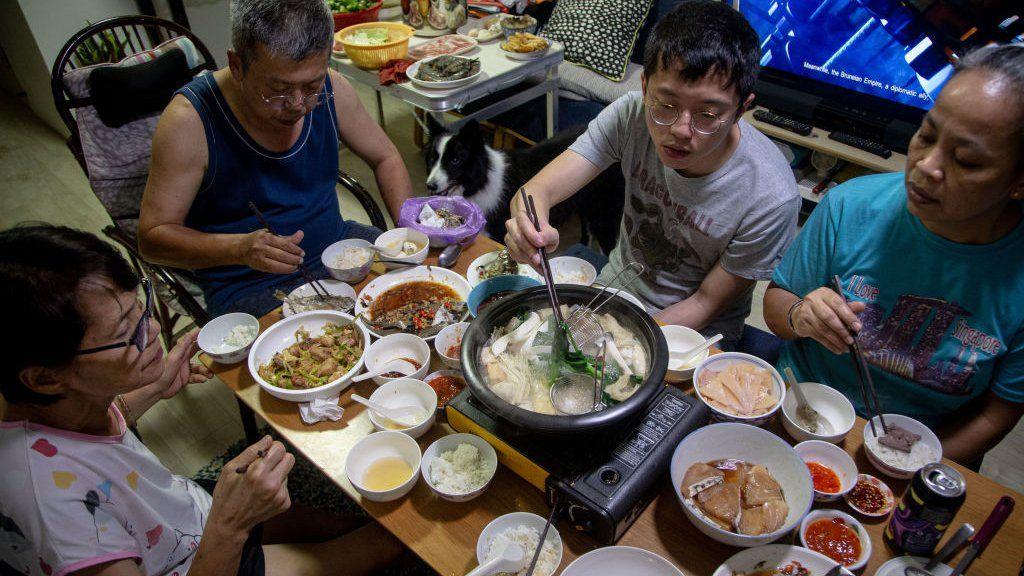 Семья принимает участие в трапезе на пароходе на семейном ужине дома накануне лунного нового года 11 февраля 2021 года в Сингапуре.
