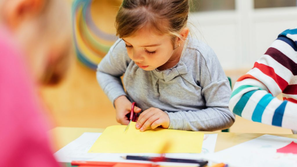 Young girl cutting yellow paper