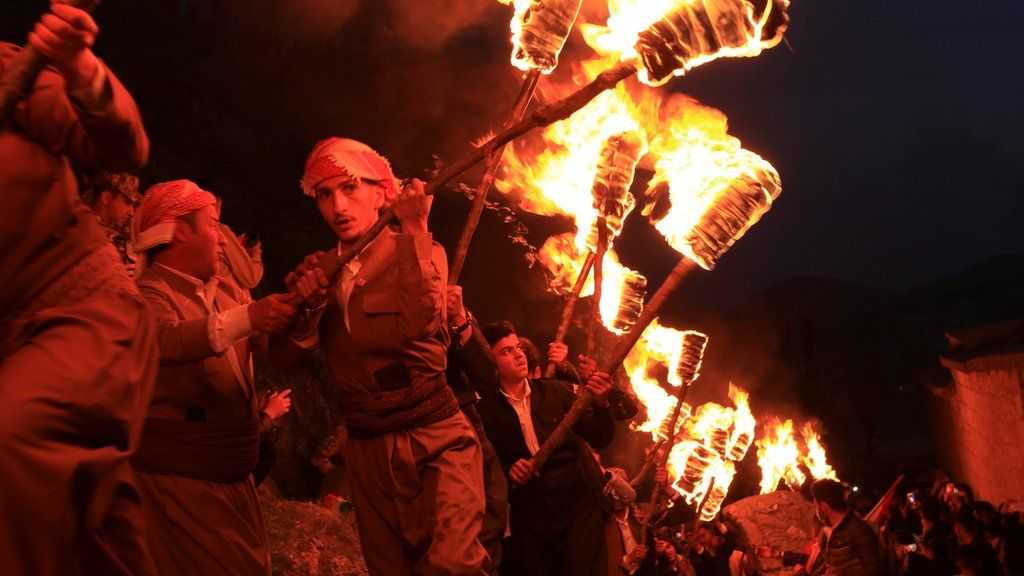Iraqi Kurdish people carry fire torches, as they celebrate Nowruz Day, a festival marking the first day of spring and the new year, amid the spread of the coronavirus disease (COVID-19), in the town of Akra near Duhok, in Iraqi Kurdistan