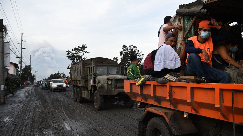 Residents aboard a government truck evacuate to a safer place after Taal volcano began spewing ash over Tanauan town, Batangas province south of Manila on January 13