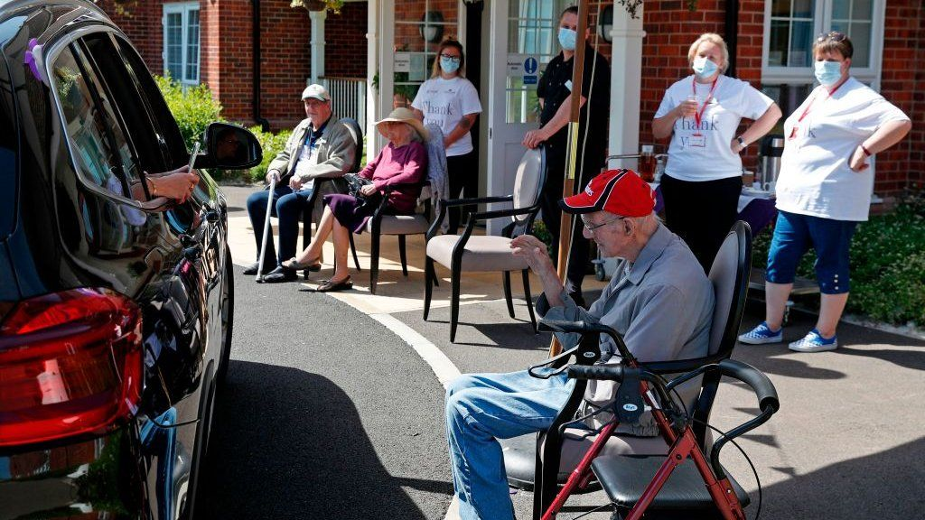 Visitor takes a picture of her granddad during a drive-through visit at Gracewell, a residential care home in Adderbury, May 28, 2020