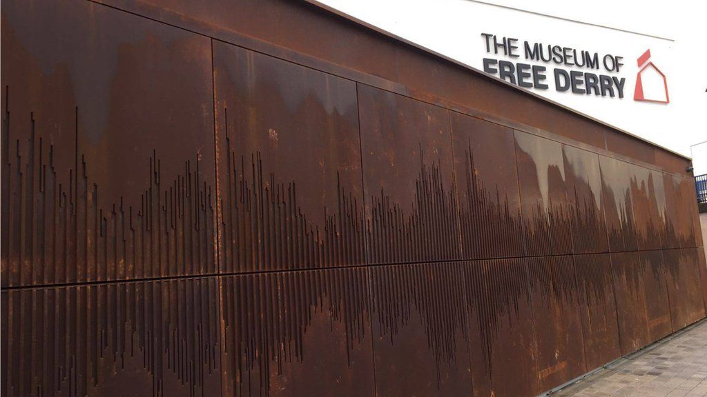 The outside wall shows a sound wave of 'We Shall Overcome'