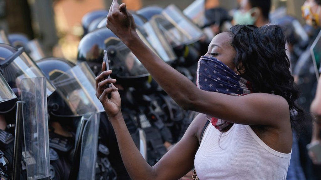 Woman with mobile phone in front of police lines at US demo