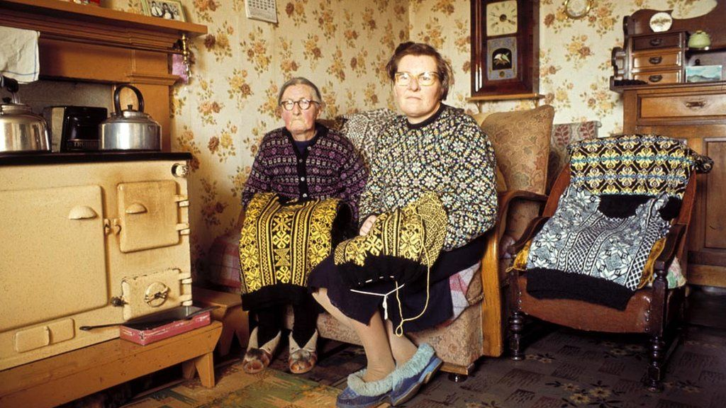 Two women knitting Fair Isle style jumpers pose in the living room of a cottage on one of the Shetland Islands in 1970.