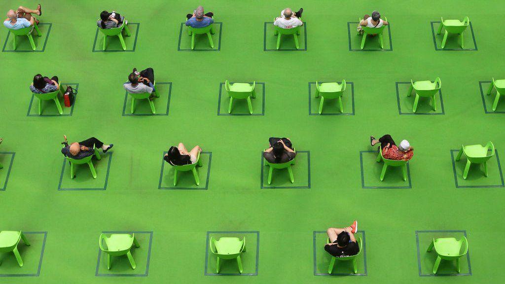 Люди сидят на стульях, отмеченных для сохранения социального дистанцирования в условиях пандемии COVID-19 19 марта 2021 года в Сингапуре.