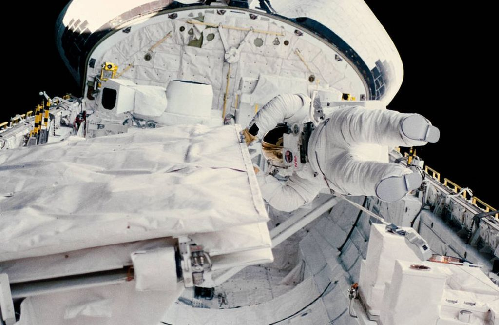 Astronaut Kathryn D. Sullivan checks the latch of the SIR-B antenna in the space shuttle Challenger's open cargo bay during her historic extravehicular activity (EVA) on Oct. 11, 1984