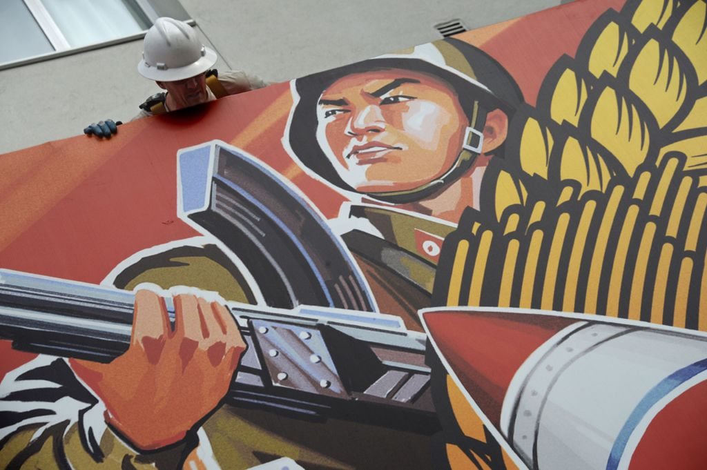 A worker takes down a poster for The Interview, after cinema chains refused to show it
