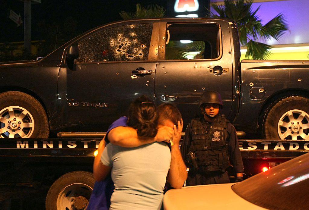 Un policía es consolado por su esposa luego de un tiroteo fatal entre narcos y policías en Culiacán