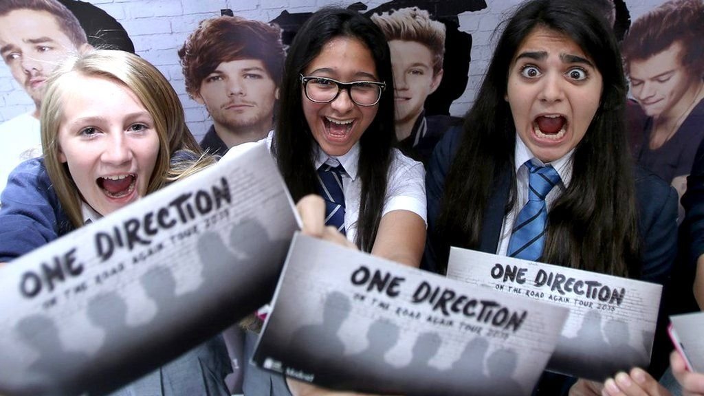 Fans hold tickets for One Direction's tour