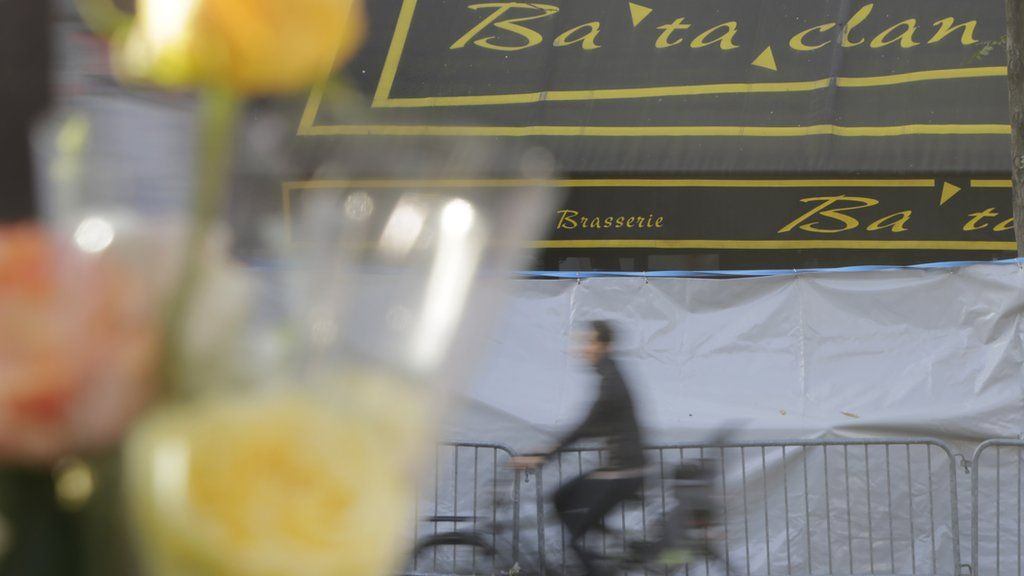 A man rides his bicycle in front of a makeshift memorial next to the Bataclan concert hall in Paris, France, Wednesday, Nov. 18, 2015