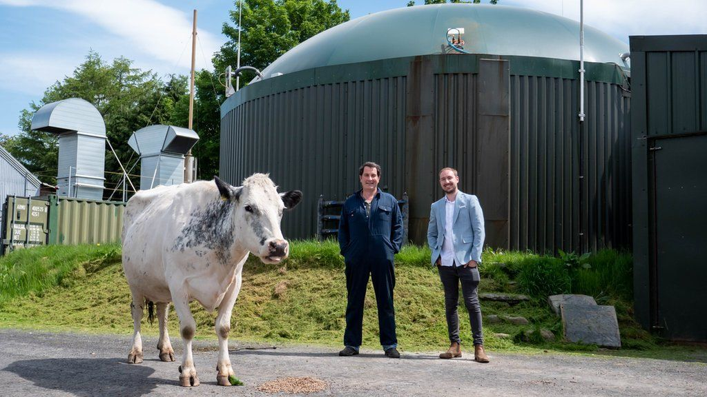 cow and farmer in front of AD plant