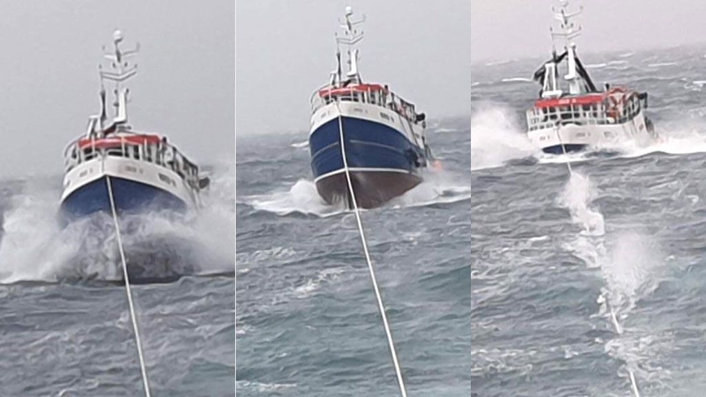 Fishing boat under tow in rough conditions