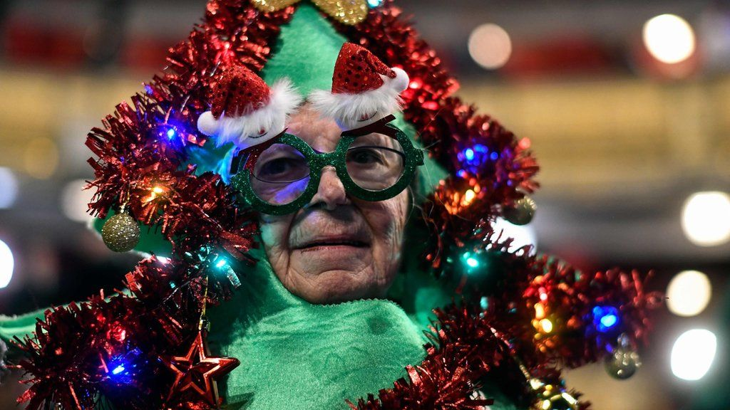 A woman dressed as a Christmas tree attends the draw at the Royal Theatre.
