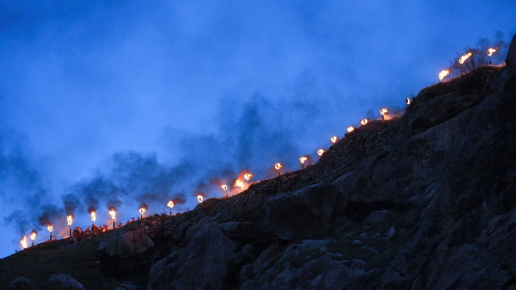 Fire torches are seen as Iraqi Kurdish people celebrate Nowruz Day, a festival marking the first day of spring and the new year, amid the spread of the coronavirus disease (COVID-19), in the town of Akra near Duhok, in Iraqi Kurdistan