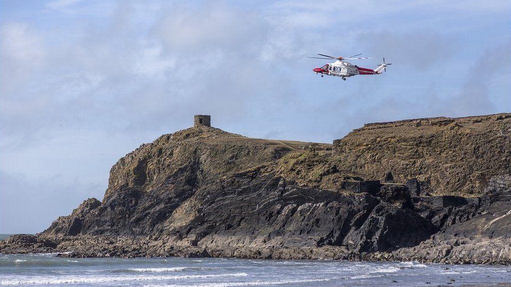 Tîm achub yn ymateb i alwad ar ôl i fachgen fynd i drafferth yn y môr ger traeth Abereiddi yn Sir Benfro // A rescue helicopter responds to an emergency call near Abereiddy beach in Pembrokeshire