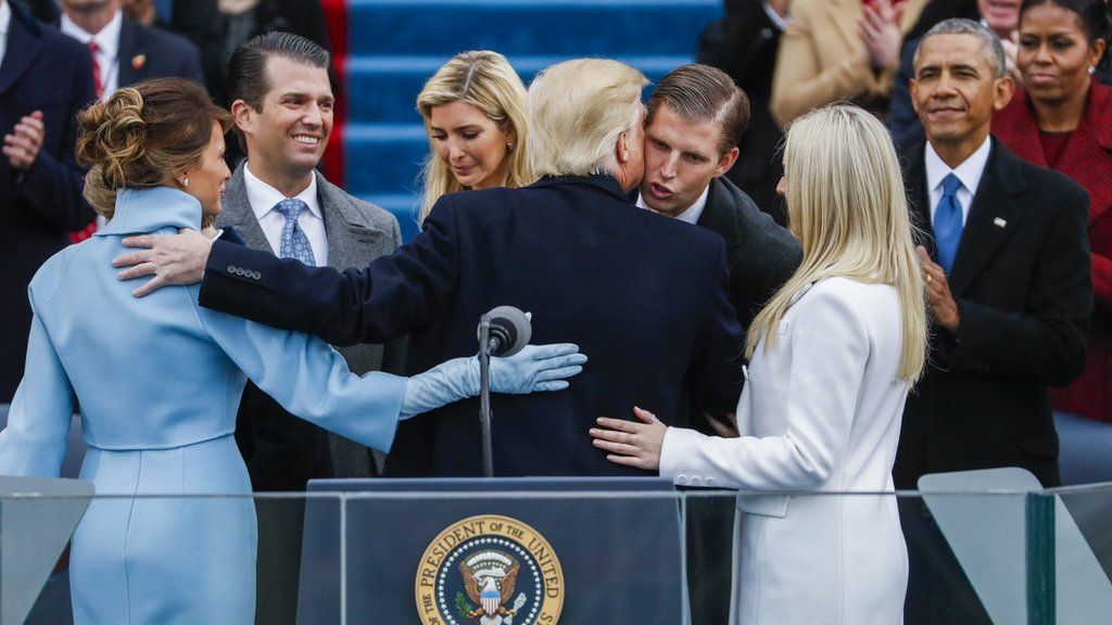 President Trump is congratulated by his family after taking the oath of office, as former President Obama and his wife Michelle look on