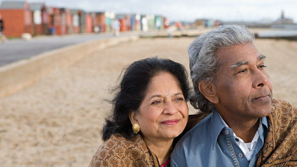 An Asian mature couple look out to the sea as they stand on the beach