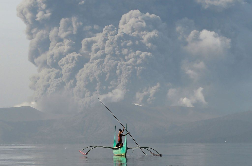 A youth living at the foot of Taal volcano rides an outrigger canoe while the volcano spews ash as seen from Tanauan town in Batangas province, south of Manila, on January 13