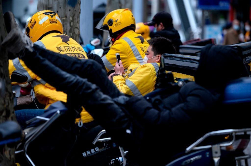 Motorcycle delivery workers wearing protective facemasks wait for orders along a street in Shanghai.