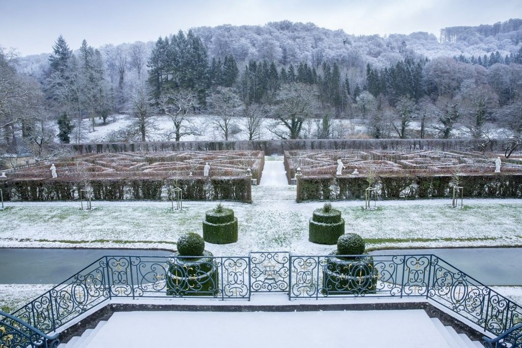 A snow-covered landscape showing a garden maze in front of a forest