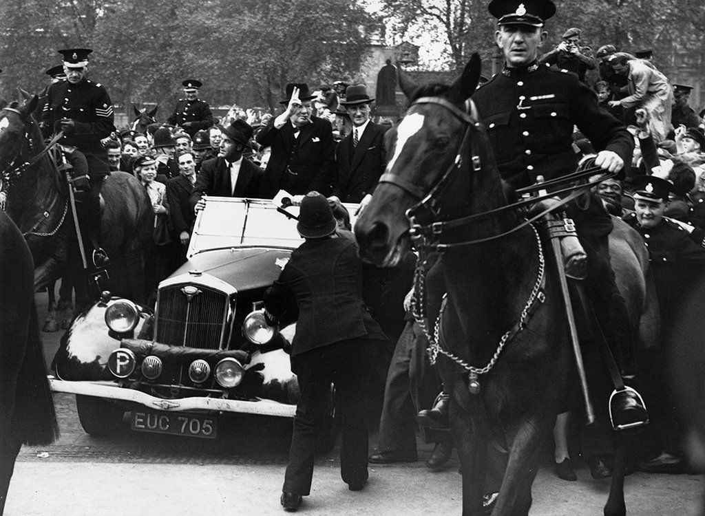 Prime Minister Winston Churchill rides in an open car to the House of Commons, surrounded by celebrating crowds on VE Day, 1945