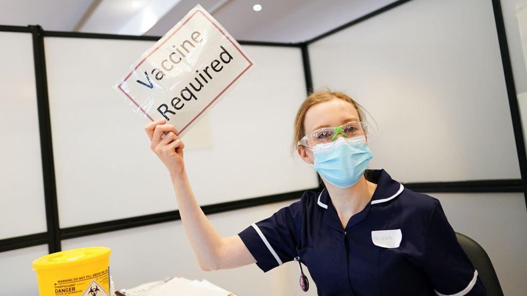Nurse holding sign - vaccine required
