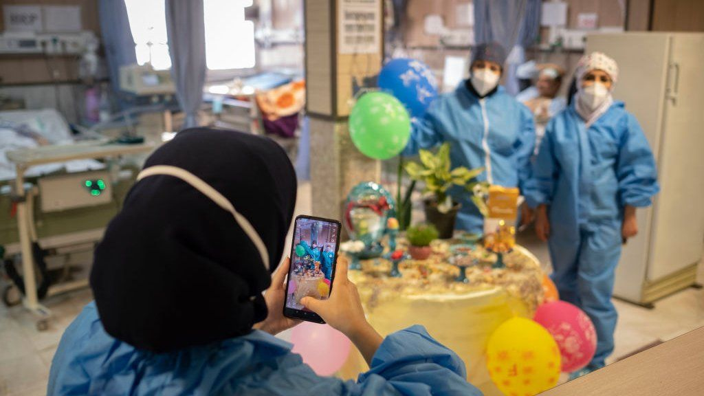 Two Iranian medical personnel wearing protective suits pose for a photograph as they stand next to a Haft-Seen (Seven-S) table, The historical symbol for the Iranian New Year, in a COVID-19 ward in Firoozabadi hospital in Shahr-e-Rey neighborhood in the south of Tehran on the day of Nowruz