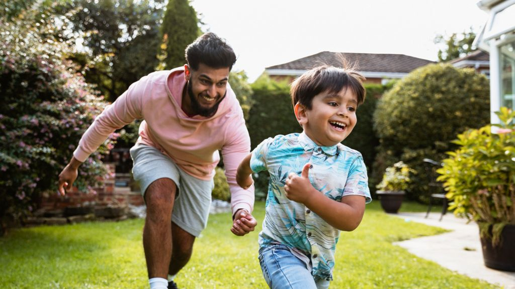 Man plays chase with a young boy in a garden