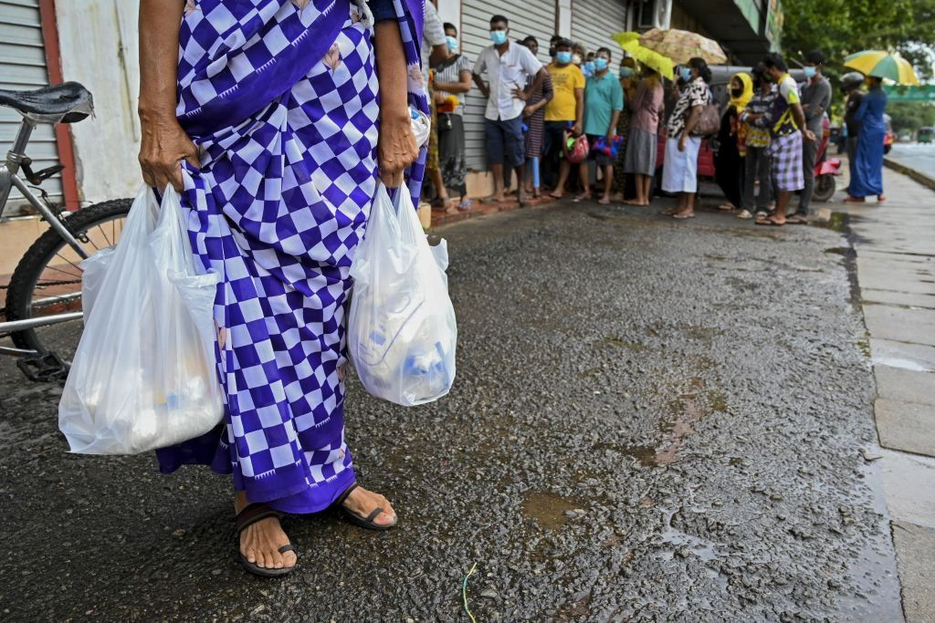 Woman carrying food bags in Colombo while people wait in queue outside a state-run supermarket