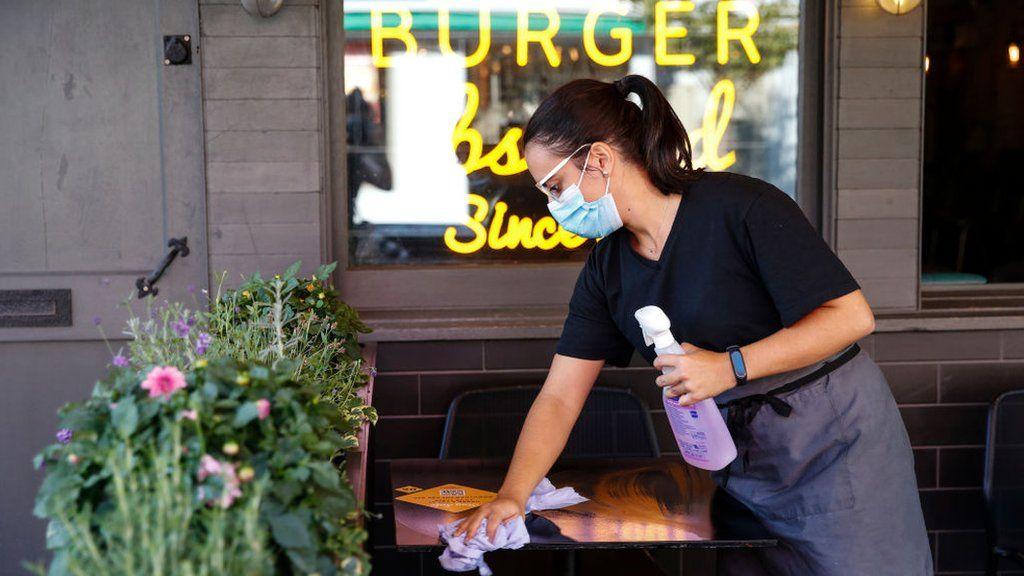 Woman wiping table at burger restaurant