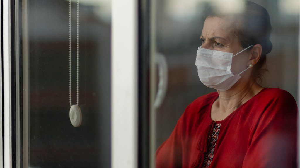 Concerned Asian woman wearing a face mask looking out of the window