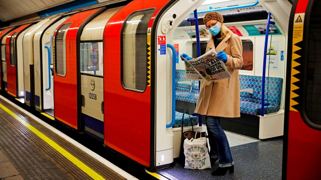 A woman wearing a mask reads a newspaper on a London Underground train, 11 May 2020